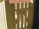 Close up of gate (open picket style) built from pressure treated lumber to protect sublevel entrance for basement stairs at home on Seminary Road, Silver Spring, MD.